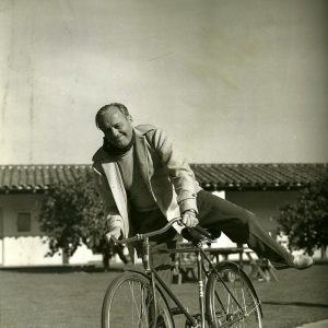 Jack Benny mounts a bike.