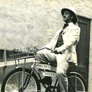 David Niven rides a bike.