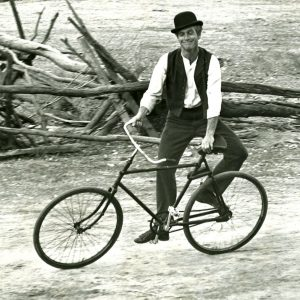 Paul Newman side-rides a bike.