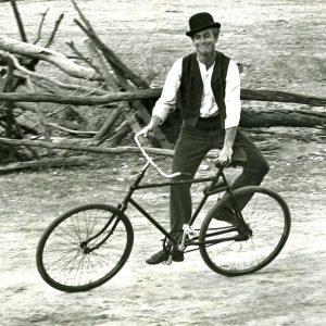 Paul Newman side-rides a bike.