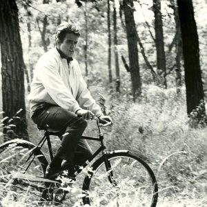 Warren Beatty rides a bike.