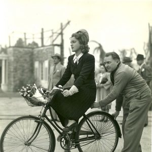 Jeanette MacDonald rides a bike, property master Harry Albiez gives a push.