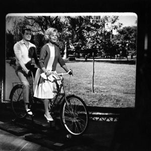 Rock Hudson and Doris Day ride a bike.
