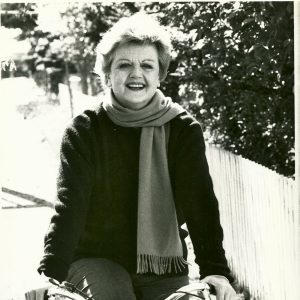 Angela Lansbury rides a bike.
