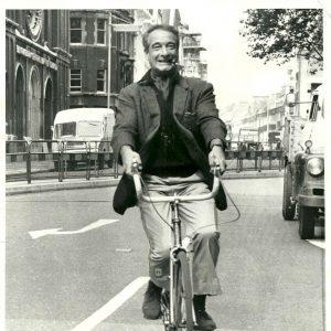 Victor Borge rides a bike.