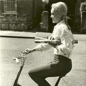 Shirley Eaton rides a bike.
