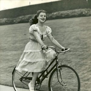 Faye Marlowe rides a bike.