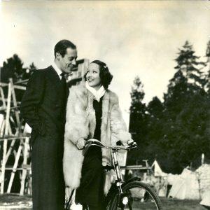 Merle Oberon rides a bike, Rex Harrison stands by debonairly.