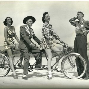 Jinx Falkenburg, Jack Benny and Peggy Diggins ride a bike. Charles Farrell wears a shirt.
