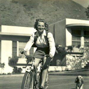 Elyse Knox rides a bike.