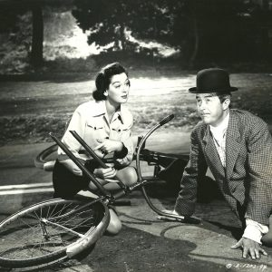 Rosalind Russell and Ray Milland crash a bike.