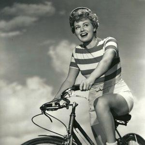 Shelley Winters rides a bike.