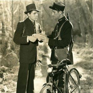 Policeman rides a bike, checks Glenn Ford's documents.