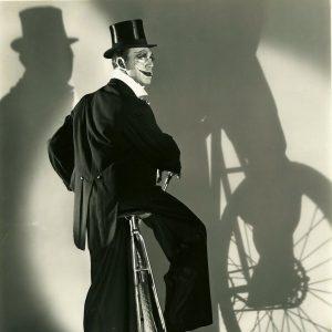 Hal Skelly rides a bike. Clownishly, noirishly.