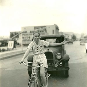 Shirley Grey rides a bike, signals left.