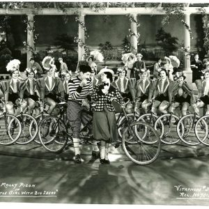 Molly Picon, Jay Velle and Vitaphone showgirls ride bikes.