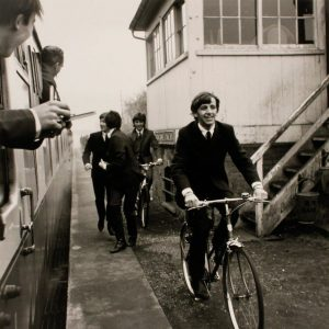 Ringo Starr and George Harrison ride bikes. John Lennon and Paul McCartney run.
