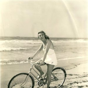 """Muriel Angelus rides a bike. LIKES IT TOUGH – Just riding a bicycle isn't enough exercise in the opinion of Muriel Angelus, blonde Paramount star. She even takes the bike down to the beach and pedals through the loose sand, which helps keep those lovely legs in trim. Muriel has done four pictures in quick succession, including """"Safari"""" and """"Down Went McGinty,"""" since she arrived in Hollywood."""