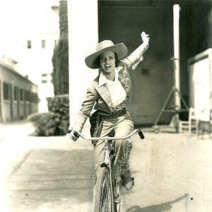 Ann Loring rides a bike, wild westily.