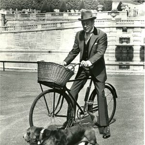 Rex Harrison rides a bike. Basset hound gallops alongside.