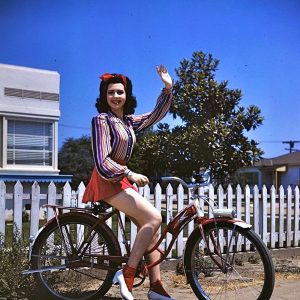 Ann Miller waves a bike.