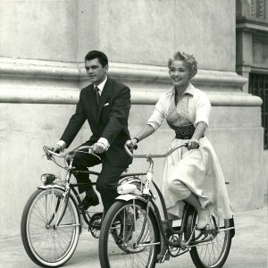 Edward Purdom and Jane Powell ride bikes.