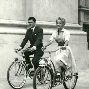 Edward Purdom and Jane Powell ride bikes.