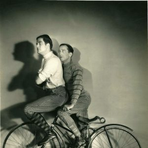 Grant Withers and Jack Mulhall ride a bike.