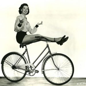 Rosalind Russell rides a bike – hands free, feet free, effortlessly.