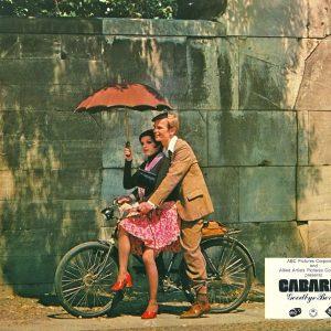 Liza Minnelli and Michael York ride a bike.