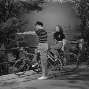Richard Greene and Vera Zorina ride bikes. And point to something in the fake shrubs.