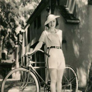 Fay Wray stands by a bike.