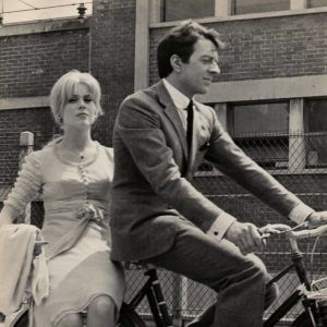 Catherine Deneuve and Jean-Pierre Cassel ride a bike.