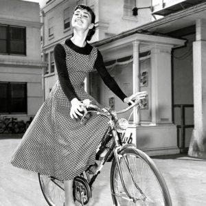 "Audrey Hepburn rides a bike.  ""Once upon a time, on the north shore of Long Island, some thirty miles from New York, there lived a small girl on a large estate…."""