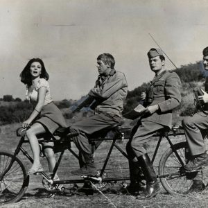 Giovanna Ralli, James Coburn, Sergio Fantoni and Dick Shawn ride a bike.