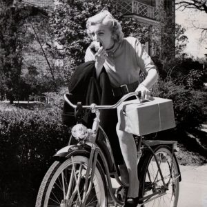 """Jan Sterling rides a bike. And eats an apple. And carries her coat. And totes a package. One of a series of eight bicycle riding """"don't""""s featuring actress Jan Sterling, photographed in May, 1951."""