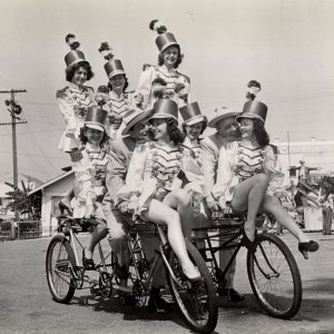 Ole Olsen and Chic Johnson ride side-by-side triplets – with seven movie majorettes.