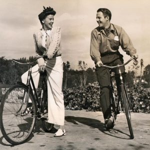 Ida Lupino and Louis Hayward ride bikes.