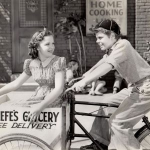 Gloria Jean and Tommy Bond ride a delivery bike.