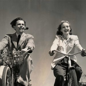 Glenn Ford and Evelyn Keyes ride bikes.