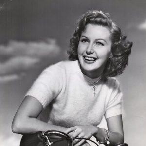 Rhonda Fleming rides a bike, radiantly.