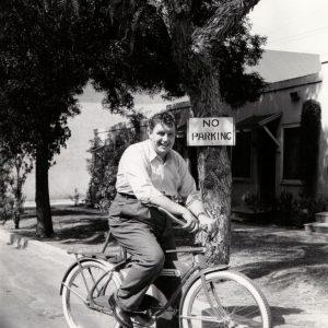 Andy Devine rides a bike.
