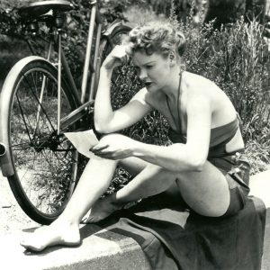 "Elaine Stritch rests her bike, reads a note, almost causes a riot.       NEW YORK, June 26—TOLD TO KEEP HER SHIRT ON – Blonde Elaine Stritch, understudy to Ethel Merman in the Broadway hit, ""Call Me Madam,"" wears halter and shorts which cause her arrest in Central Park. Today she was fined $1 and told by Magistrate Emilio Jones, ""A beautiful girl like you could cause a small riot and cause a large crowd to collect by removing your shirt."" ""Well,"" she replied, ""I was there all day and nothing happened."" (AP, 1951)"