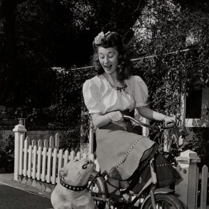 Joan Davis rides a bike, Big Boy the bulldog sits, stares.