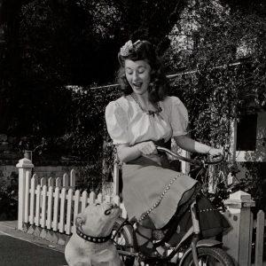 Joan Davis rides a bike, Big Boy the bulldog sits, stares.