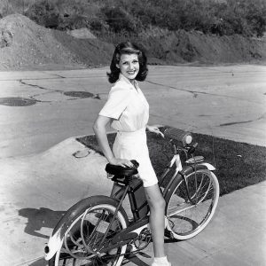 Rita Hayworth rides a bike.