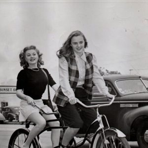 """Suzi Crandall and Leza Holland ride a bike. NOTHING CAN STOP 'EM –HOLLYWOOD, CALIF. Warner Bros' actresses Leza Holland and Suzi Crandall took the Los Angeles transportation strike in stride. The two girls, who usually ride the bus to work in the morning, hired a two-seater tandem and bicycled 12 miles from Beverly Hills to the studio. They arrived in time for their first scene in """"Stallion Road."""" Acme 5/3/46"""