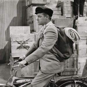 Bob Hope rides a bike.