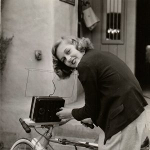 "Patricia Ellis rides a bike, plays a radio. MUSIC WITH HER BIKE RIDES: PATRICIA ELLIS HAS A RADIO WITH BATTERIES AND EVERYTHING ATTACHED TO HER BICYCLE SO THAT SHE CAN LISTEN TO MUSIC ON THE AIR WHEN SHE RIDES HOME FROM THE FIRST NATIONAL STUDIO WHERE SHE IS FILMING ""THE WORLD CHANGES."" First National Pictures, 1933"