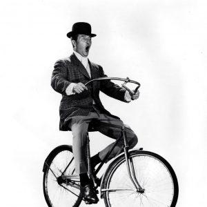 Ray Milland rides a bike, handlebars free.